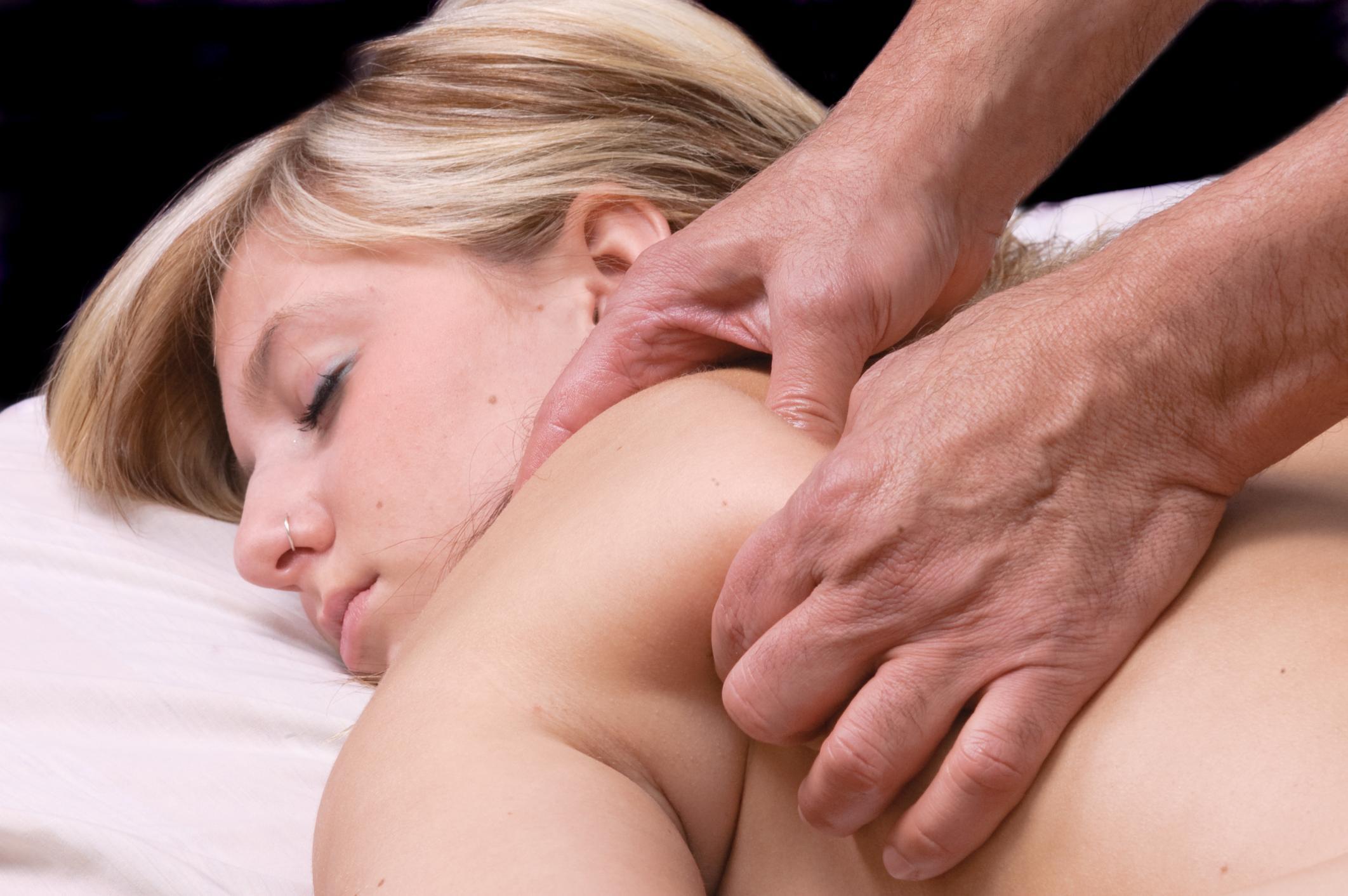 Massage therapist massaging a woman's shoulder