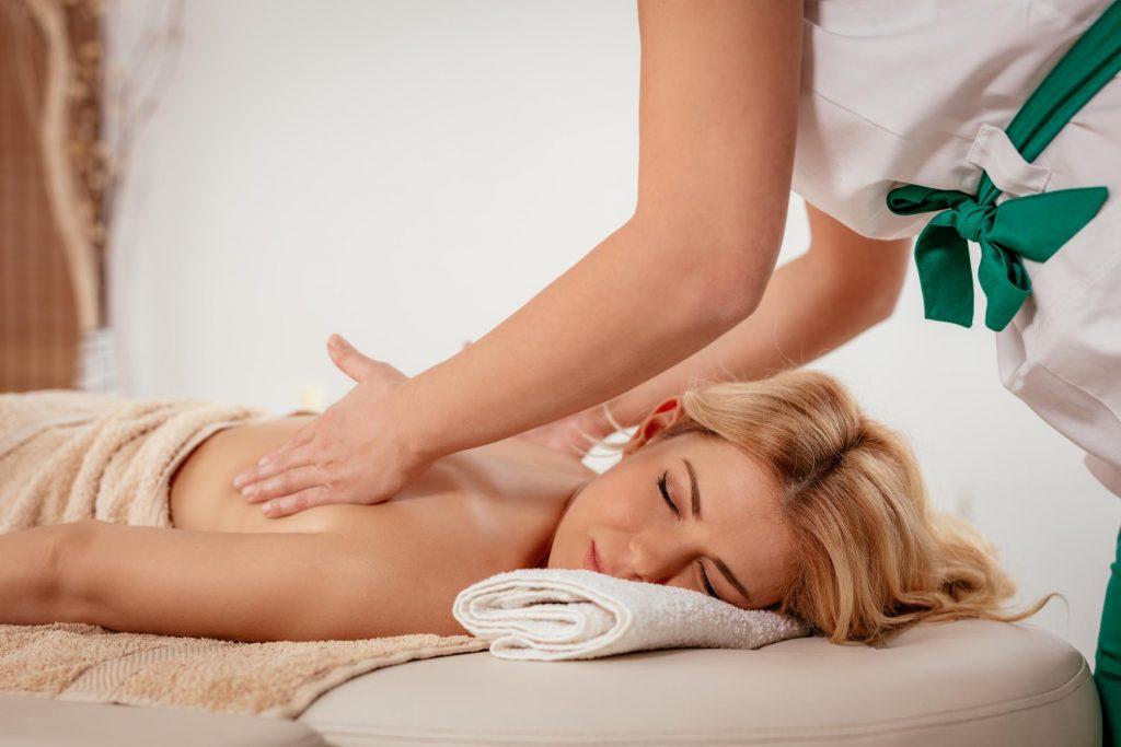 Massage therapist massaging woman's back