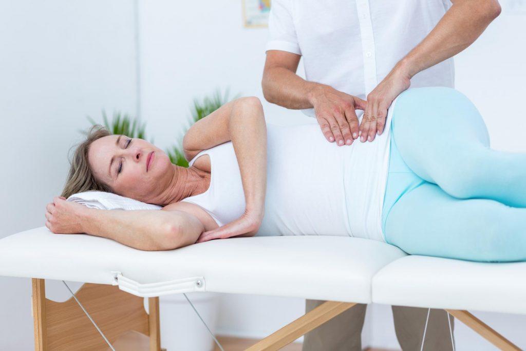 Massage therapist massaging woman's thighs