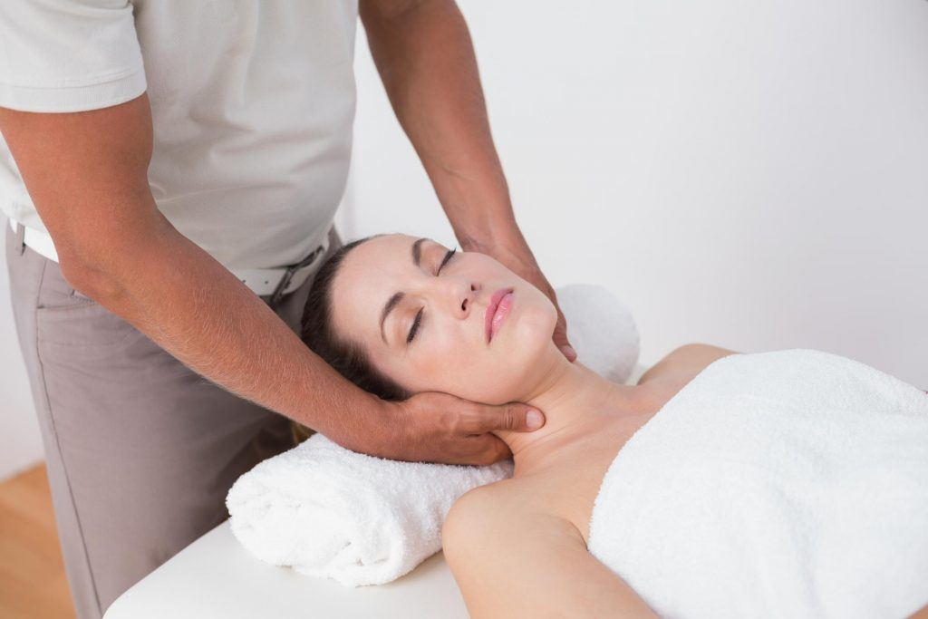 Massage therapist massaging woman's neck